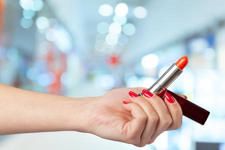 salon: Womans hand holds lipstick