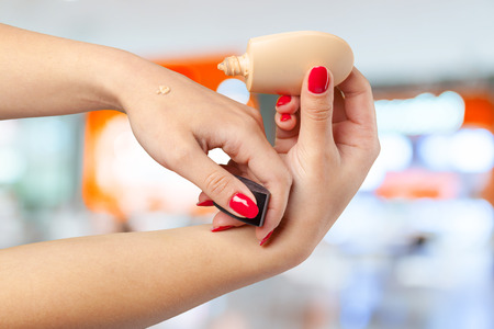 hand of young girl holding cream bottle