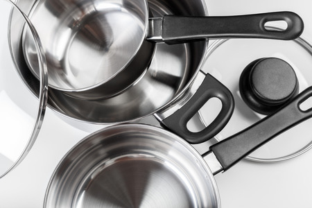 Stainless steel pots and pans isolated on white