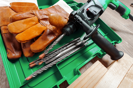 Electric hammer drill lies on a wooden table
