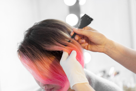 Hairdresser does hair style of woman