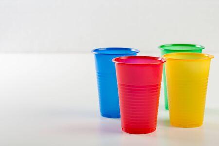 Multicolor disposable plastic glasses isolated on white background