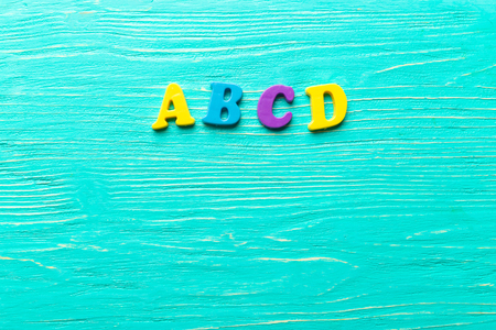clutter: Multiple colored letters on wooden table