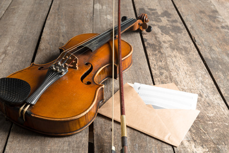 Sheet music and violin on wooden table Stock Photo