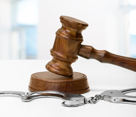 Gavel and handcuffs on wooden table background