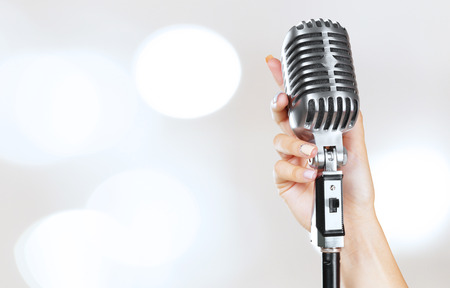 Womans hand on retro microphone
