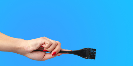 Woman hand with a hair dressers tools and accessories isolated on color background