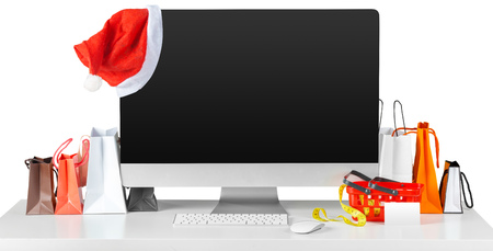 E-commerce concept. Computer monitor screen on table with shopping accessories Stock Photo