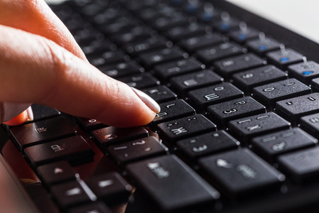 keyboard. Finger pressing button. Stock Photo