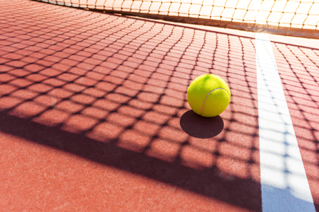 tennis ball on a tennis court with net