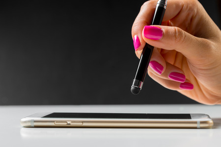 woman working with pen on smart mobile phone
