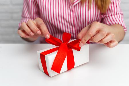 Female hands holding gift box.