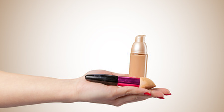 Woman hand with a foundation cosmetic tool isolated on color background Imagens
