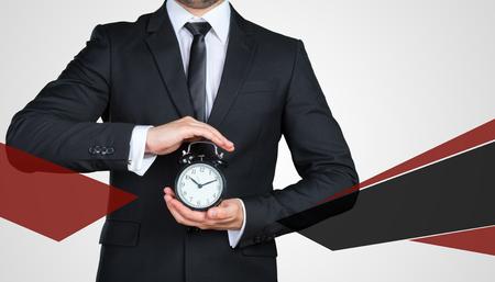 Unrecognizable businessman showing you black alarm clock. Business concept