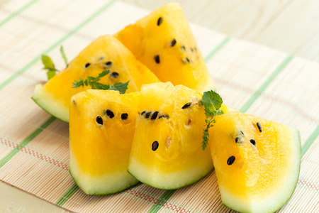 Yellow watermelon sliced on wooden background