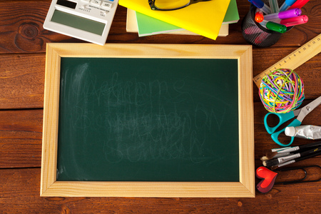 School supplies on a wooden table and blackboard Stock Photo