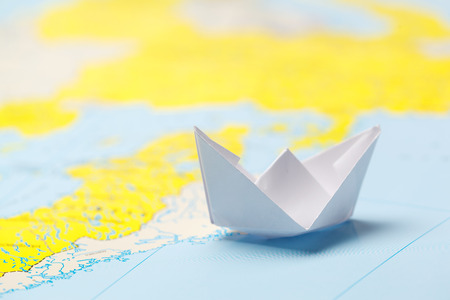 Origami paper ship on a map. Leadership and travelling concept