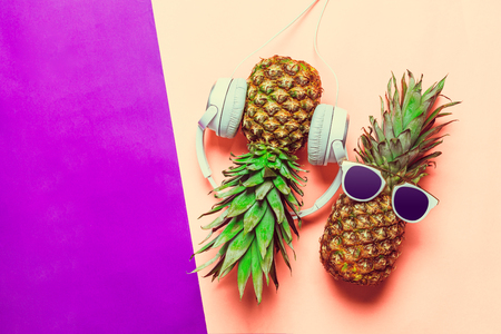 pineapple on colored paper with glasses Imagens