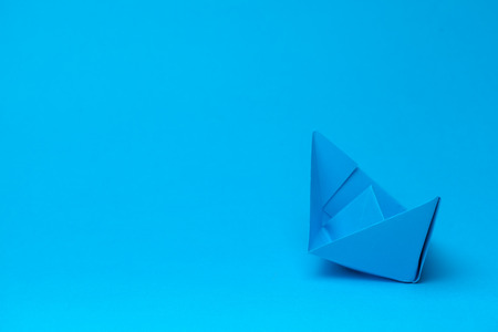 Origami paper boat on blue background Stock Photo