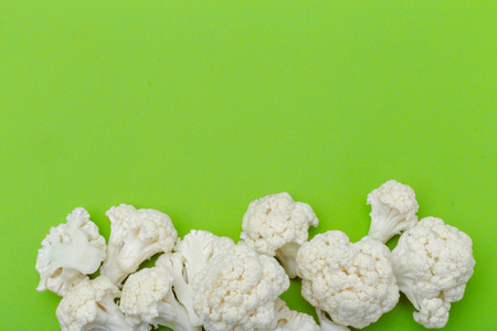 Piece of cauliflower isolated on green background