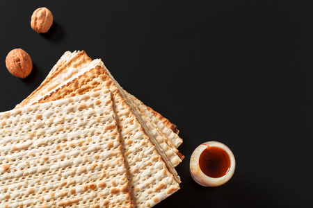 A photo of matzah or matza pieces  on black background. Matzah for the Jewish Passover holidays. Place for text, copy space