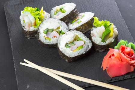 Japanese restaurant, sushi roll on black slate plate. Imagens