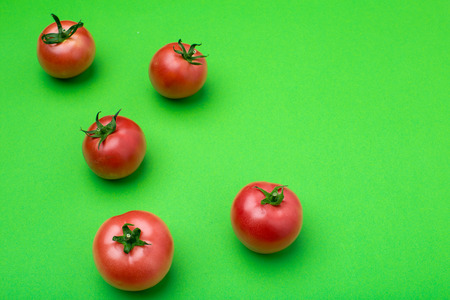 red tomatos on color background