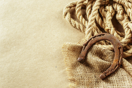 Old horseshoe and rope on wooden boards Stock Photo