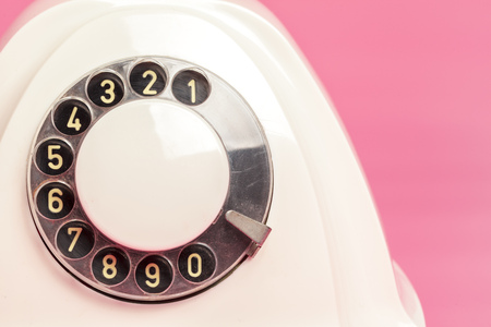 Retro white telephone on pink background