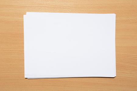 Weiße Visitenkarte auf Holztisch. Leeres Porträt A4. Standard-Bild