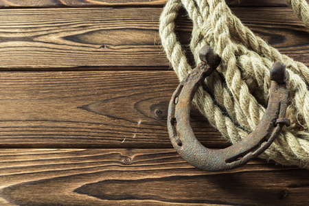 Old horseshoe and rope on wooden boards 写真素材