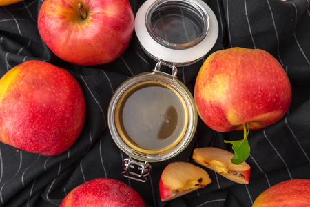 Jewish holiday Rosh Hashanah background with honey and apples on wooden table.