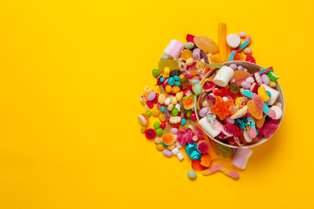 colored candies on yellow background