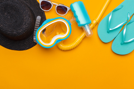 Composition of beachwear and accessories on a yellow background 免版税图像