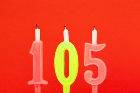 Colorful burning birthday candle  on red background Stock Photo