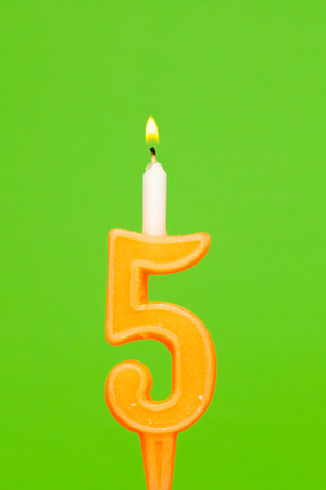 Colorful wax birthday candle  on green background Stock Photo