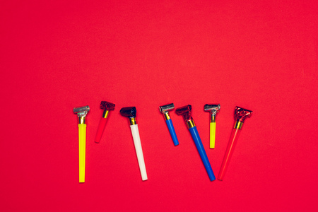 Colorful party blowers or noisemakers on colored background