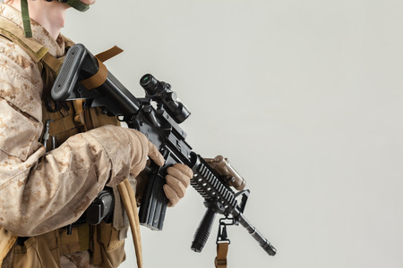 Soldier in camouflage holding rifle Stock Photo