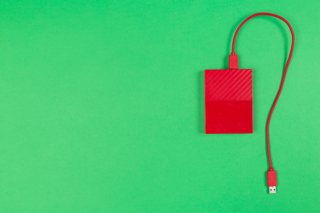 Red external harddrive disk on colored background