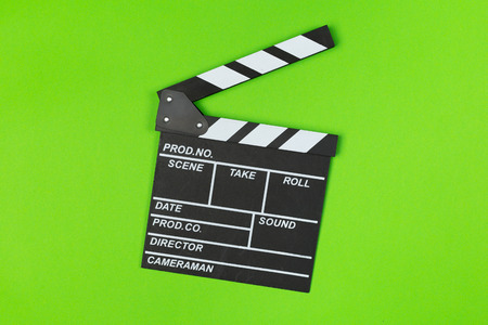 Film clapper board on green background top view Foto de archivo