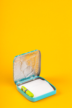 Metal box for women's hygienic supplies on bright yellow background
