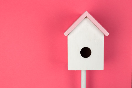 Wooden birdhouse on pink background top view