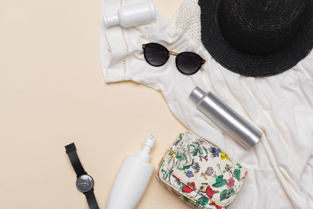 Composition of white dress, black straw hat, sunglasses, handbag and other accessories on pastel background top view Banque d'images