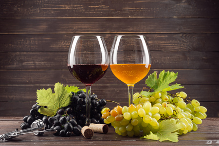wine glass and bunch of grapes on wooden table Imagens