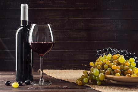 Botella de vino y uva en mesa de madera Foto de archivo