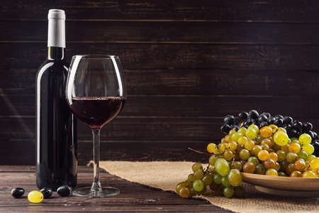 Wine bottle and grape on wooden table 写真素材 - 111527211