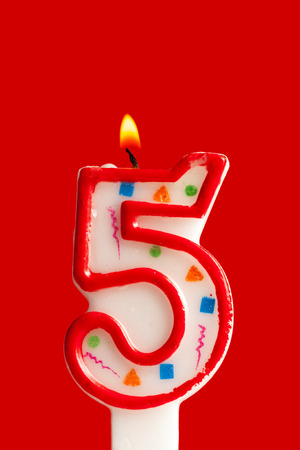 Colorful burning birthday candle  on red background Banco de Imagens