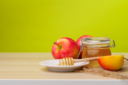 Jewish holiday Rosh Hashanah background with honey and apples on wooden table. Stock Photo