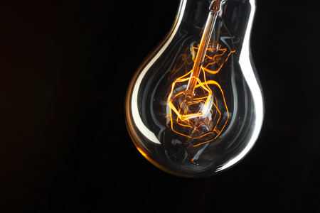 A classic Edison light bulb on dark background with space for text Imagens