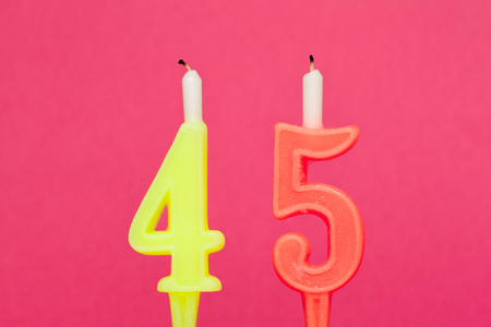 Colorful wax birthday candle  on pink background 스톡 콘텐츠